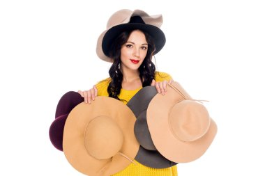 portrait of beautiful woman holding female hats isolated on white