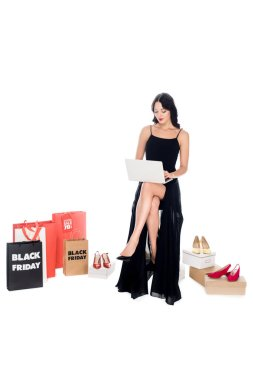 young woman in black dress using laptop with shopping bags and shoes behind isolated on white, online shopping and black friday concept