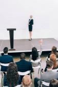 vysoký úhel pohledu přednášející pohledu mnohonárodnostní publikum během semináře v konferenční hale, účastník zvyšovat ruku