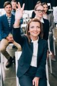 usměvavá podnikatelka s rukou se chtějí na něco zeptat během obchodní seminář v konferenčním sále