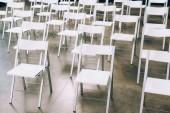 zblízka pohled uspořádány prázdné bílé židle v konferenčním sále