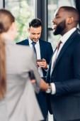 szelektív összpontosít üzletember használ smartphone, miközben többnemzetiségű kollégák beszél hivatal