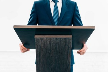 cropped image of lecturer standing at podium tribune during seminar in conference hall