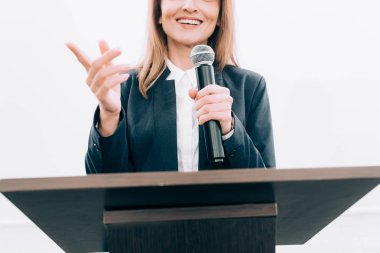 cropped image of smiling speaker gesturing and talking at podium tribune during seminar in conference hall