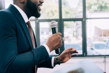 cropped image of smiling african american speaker talking into microphone during seminar in conference hall