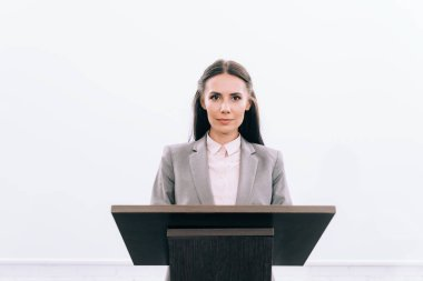 attractive lecturer standing at podium tribune during seminar in conference hall and looking at camera
