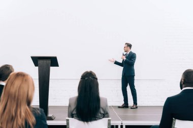 handsome speaker talking during seminar in conference hall and pointing on screen