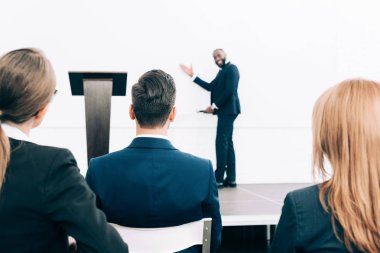 selective focus of smiling african american speaker pointing on screen in conference hall