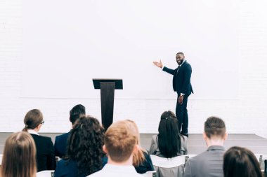 smiling african american lecturer talking to audience during seminar in conference hall and pointing on screen