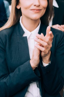 cropped image of businesswoman applauding during seminar in conference hall