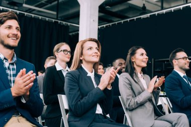 smiling multiethnic businesspeople applauding during business seminar in conference hall