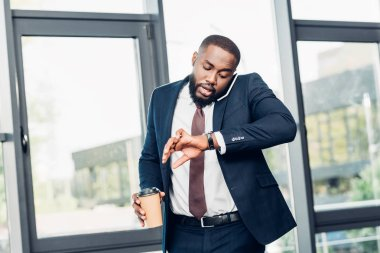 african american businessman with coffee to go checking time while having conversation on smartphone in conference hall