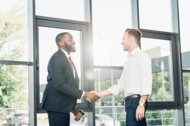 smiling multiracial business colleagues shaking hands in conference hall