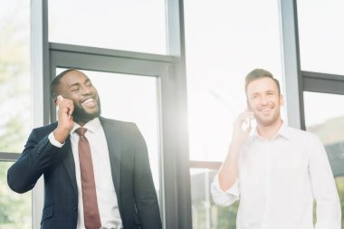 smiling multicultural businessmen talking on smartphone in office