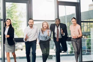 emotional multiethnic businesspeople running in conference hall