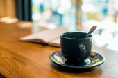 cup of coffee with spoon on wooden tabletop in cafe