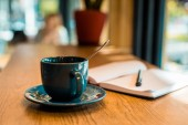 Fotografie cup of coffee with spoon and open notebook with pen on wooden tabletop in cafe