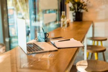laptop, smartphone, notebook and cup of tea on wooden cafe counter