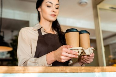 low angle view of attractive waitress in apron holding coffee in paper cups in cafe