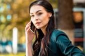 portrait of beautiful businesswoman talking by smartphone on street