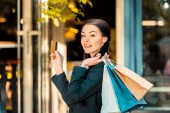 Fotografie smiling beautiful woman holding credit card and shopping bags on street near store