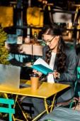 Fotografie atraktivní čtení knihy během přestávky na kávu na terase restaurace s notebookem na volné noze