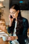 krásná obchodnice mluví na smartphone a drží šálek kávy v kavárně