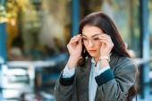 beautiful brunette woman in trendy jacket and eyeglasses