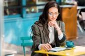 Fotografie krásné volné noze a na terase restaurace s planner, smartphone a šálek kávy