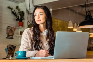 attractive brunette freelancer working with laptop in cafe with coffee cup