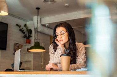 attractive bored freelancer working on laptop with coffee to go in cafe