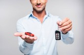 cropped shot of smiling adult man holding car alarm remote and toy red car isolated on white