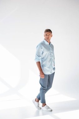 handsome adult man in stylish clothes standing on white