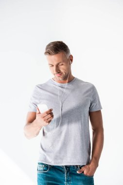Attractive adult man in blank grey t-shirt listening music with smartphone and earphones isolated on white stock vector