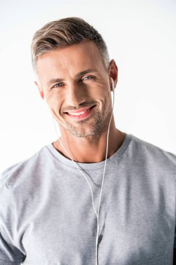 smiling adult man in blank grey t-shirt and earphones looking at camera isolated on white