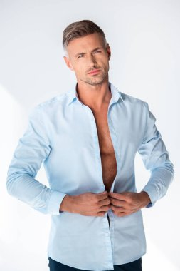 sexy macho buttoning shirt and looking at camera isolated on white
