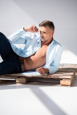 attractive adult man with unbuttoned shirt lying on wooden pallet on white and looking away