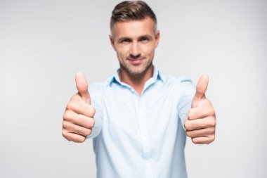 Smiling adult man in shirt showing thumbs up and looking at camera isolated on white stock vector