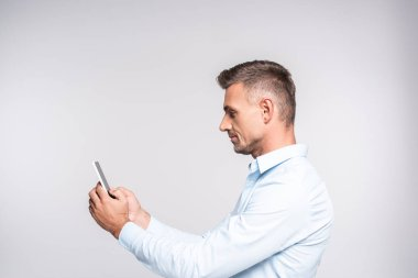 Side view of handsome adult man using smartphone isolated on white stock vector