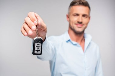 close-up shot of smiling adult man holding car alarm remote isolated on white