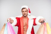 Fotografie handsome man in santa costume holding shopping bags and smiling at camera isolated on grey
