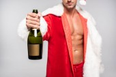 Fotografie cropped shot of sexy santa holding bottle of champagne with blank label isolated on grey