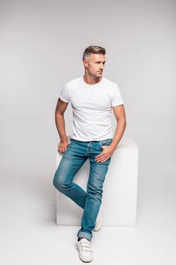 Handsome man in white t-shirt and denim pants sitting and looking away on grey stock vector