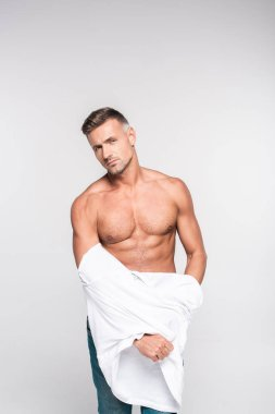 sexy muscular man taking off t-shirt and looking at camera isolated on grey