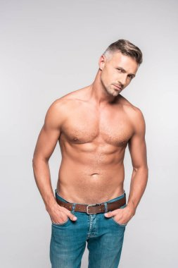 portrait of handsome shirtless man in denim pants looking at camera isolated on grey