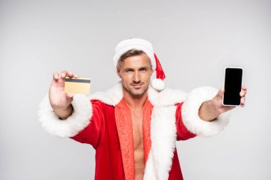 handsome smiling man in santa costume holding credit card and smartphone with blank screen isolated on grey
