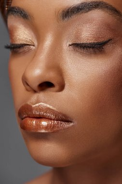 portrait of attractive african american model with eyes closed isolated on grey