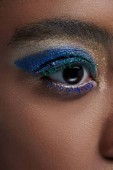 Fotografie partial view of african american woman with bright blue eye shadow