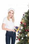 Fotografie portrét veselé ženy v santa claus čepice s zabalené dárky u vánočního stromu izolované na bílém