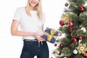 oříznutý snímek usmívající se žena s zabalené dárky u vánočního stromu izolované na bílém